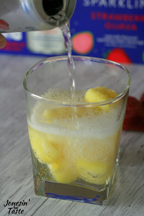 DASANI Sparkling being poured into a glass with frozen pineapple