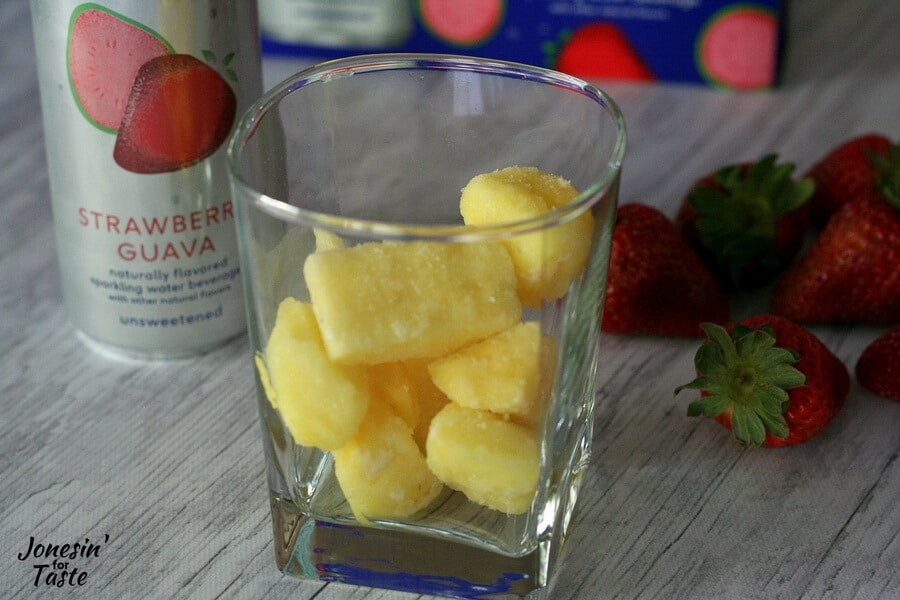 A glass of frozen pineapple with strawberries in the background