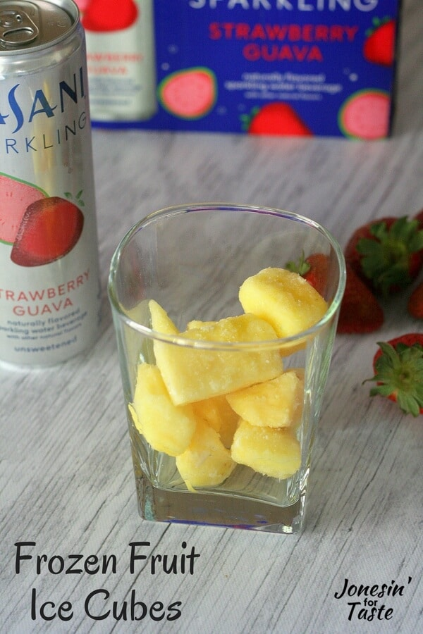 A glass with frozen pineapple in it alongside DASANI Sparkling