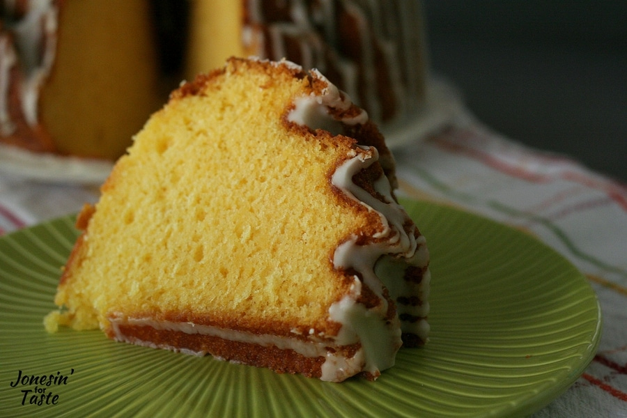 A slice of easy orange pound cake on a plate with drizzled icing on top