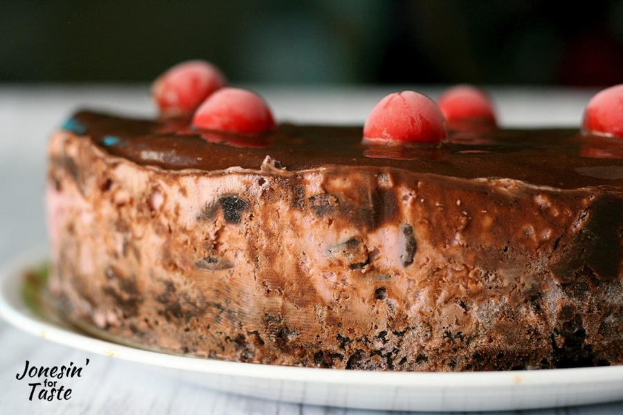 A Cherry Chocolate Ice Cream Cake with Brownie Base topped with chocolate sauce and cherries