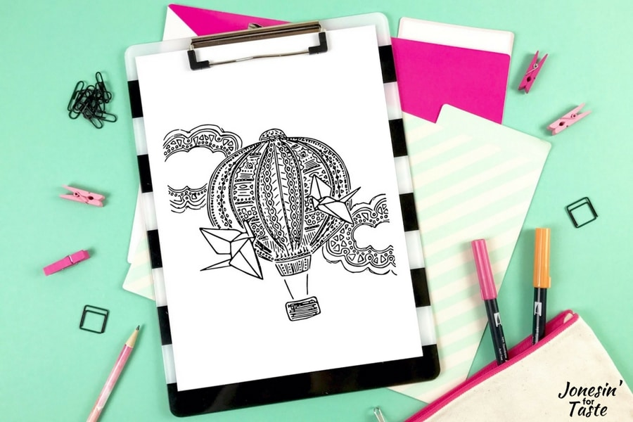 A Hot Air Balloon coloring page on a clipboard on a desk with various coloring supplies around it.
