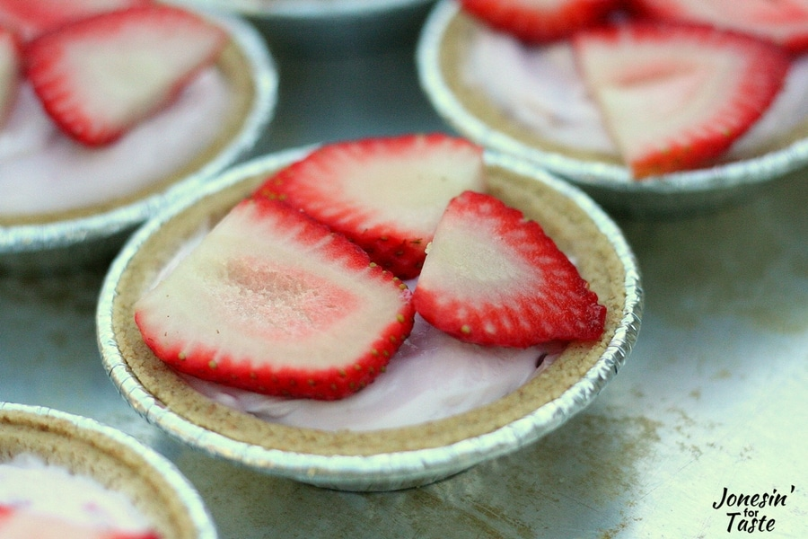 A closeup shot of a Mini No Bake Strawberry Cheesecake topped with sliced strawberries