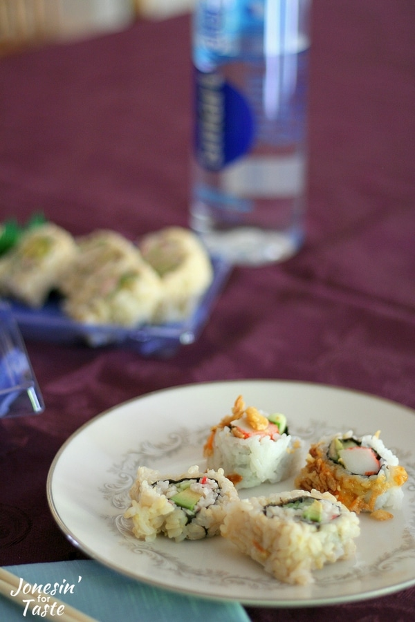 A plate of sushi on a purple tablecloth with a bottle of water and a container of sushi in the background