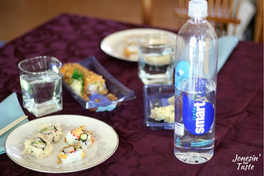 plates of sushi on a table with a bottle of smartwater in the forefront