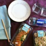 Cloth napkins, chopsticks, china plates, glasses, smartwater, and containers of sushi on a purple tablecloth