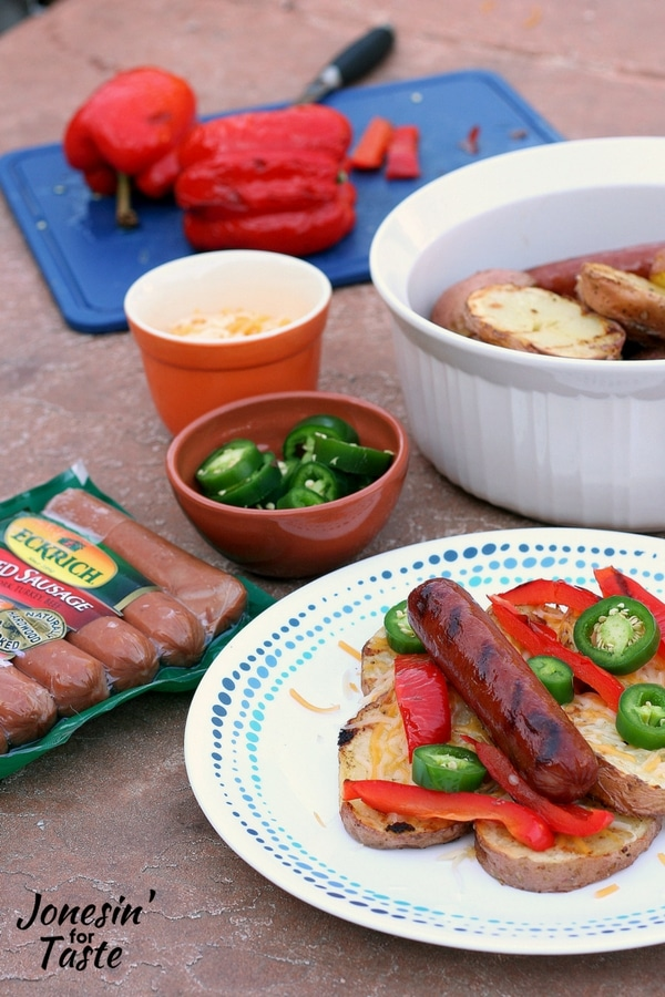 A plate of grilled smoked sausage and potatoes with toppings with a package of smoked sausages, and bowls of toppings surrounding the plate with a dish of grilled potatoes in the background