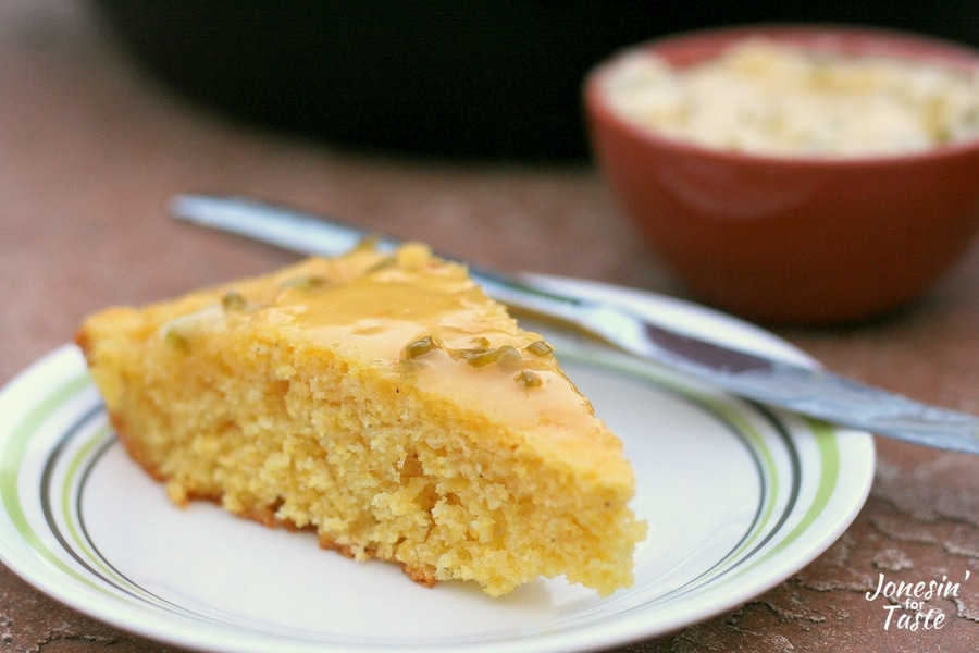 A slice of cornbread with jalapeno honey butter on a plate and a knife and jalapeno honey butter in a bowl behind it.