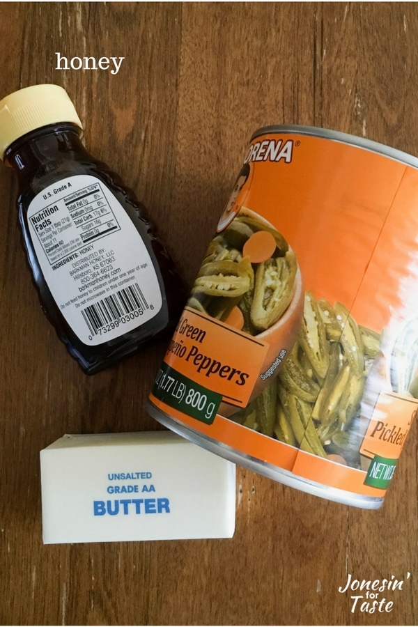 A container of honey, a stick of butter, and a can of sliced jalapeno peppers