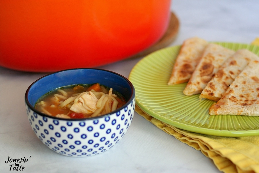 A blue bowl of quick salsa soup with an orange pot and green plate with quesadillas in the background