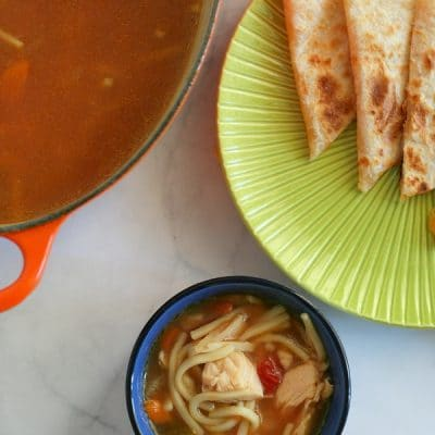 A small bowl of salsa soup next to a green plate with triangles of quesadilla and a large pot of soup next to it.