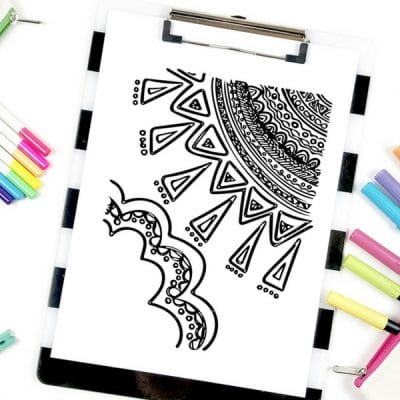 A sun coloring page on a clipboard surrounded by coloring supplies