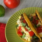Two breakfast tacos on a green plate