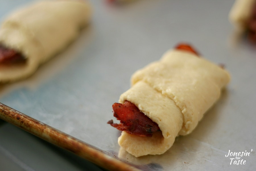 Uncooked easy bacon croissants on a cookie sheet ready to be put in the oven