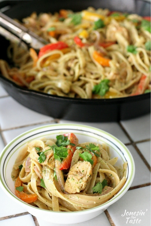 A bowl of chicken fajita pasta with cilantro lime sauce in front of a large cast iron pan full of chicken fajita pasta.