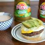 A Huevos Rancheros Burger topped with avocado served up with a dish a salsa spread with 2 bottles of Pace Salsa in the background.