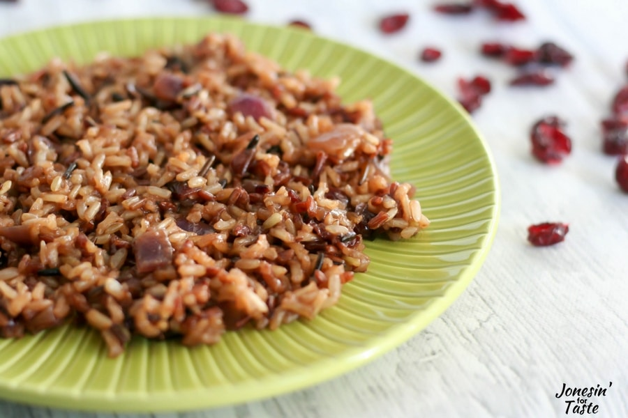 A large helping of Orange Cranberry Wild Rice on a green plate with dried cranberries in the background.