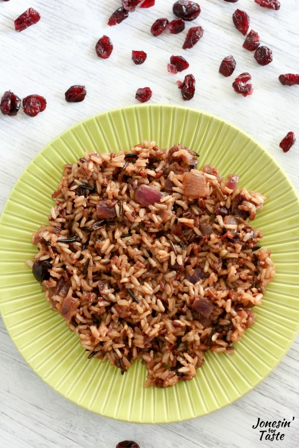 Orange Cranberry Wild Rice on a green plate on a white wooden table.