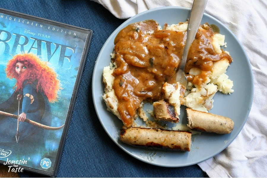 A bite of bangers and mash on a plate next to a DVD of Brave and a white napkin