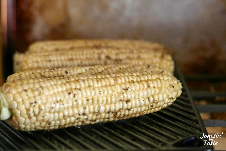 Cobs of corn on a grill brushed with cumin butter flavored coconut oil