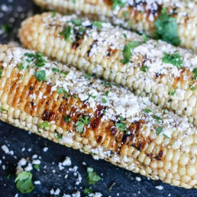 Grilled cumin corn sprinkled with cotija cheese and cilantro with beautiful char marks