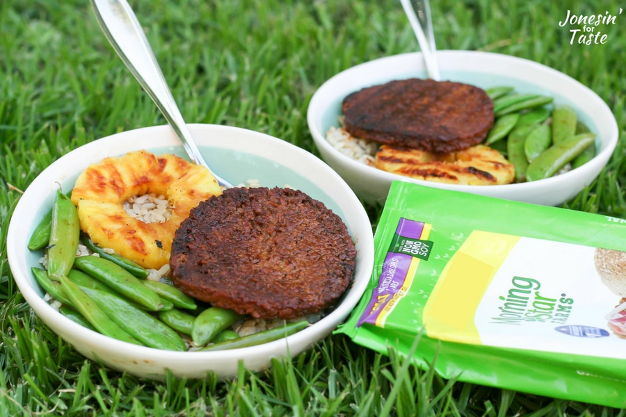 Two Teriyaki Veggie Burger Bowls and forks sitting on the grass