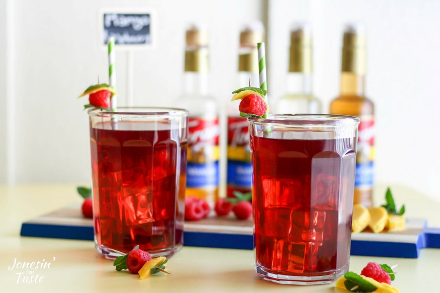 Mango Raspberry Herbal Iced Tea in glass cups with garnishes and straws