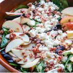 Spring salad mix topped with sliced apples, goat cheese crumbles, and bacon crumbles.