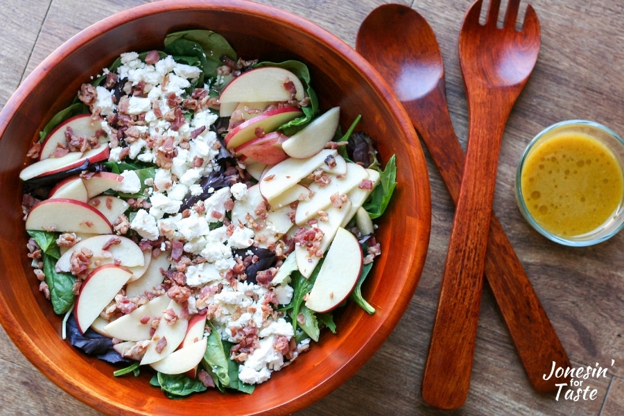 A bowl of Apple Bacon Salad next to salad tongs and a bowl of dressing.