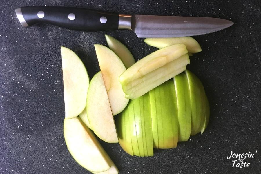 A knife next to sliced granny smith apples