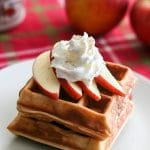 A stack of chai spiced apple waffles with whipped cream next to whole apples and maple syrup