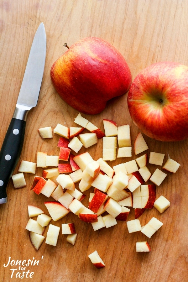 Diced apples and a knife on a cutting board