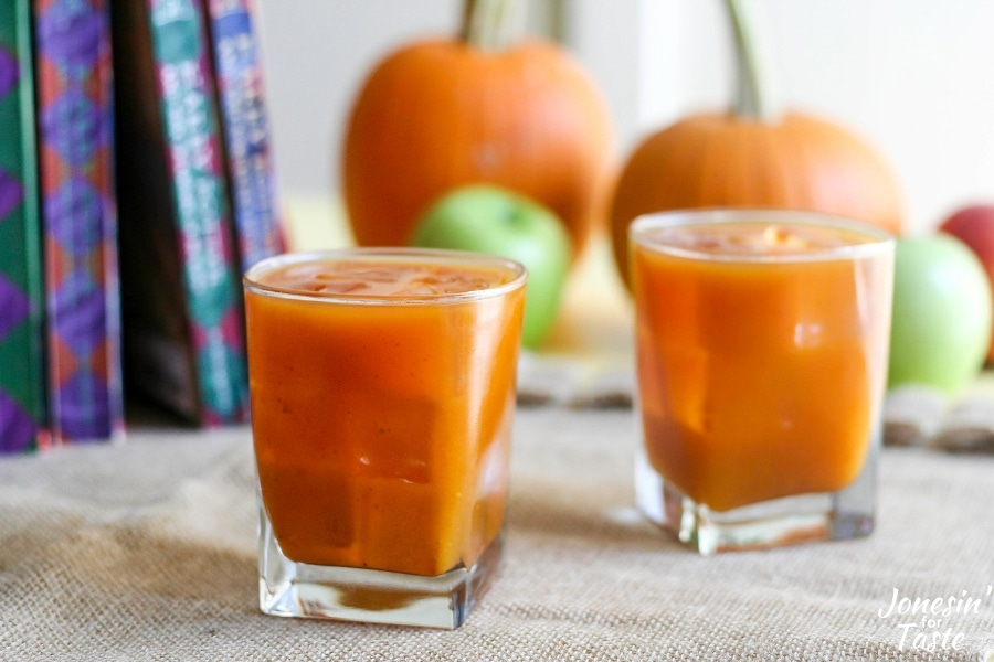 Two glasses of ice cold pumpkin juice on a table with pumpkin in the background