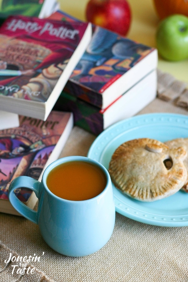 Pumpkin pasties, hot pumpkin cider, and Harry Potter books on a table.
