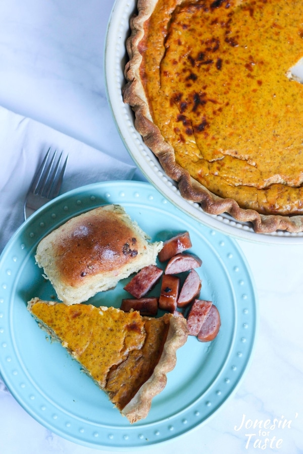 A slice of pumpkin quiche on a blue plate with a roll and smoked sausage