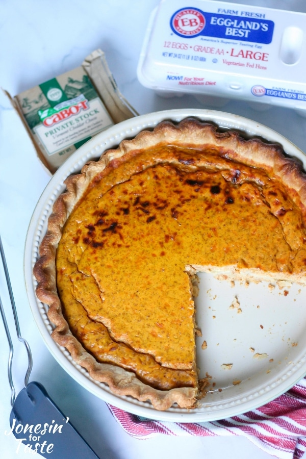 A pumpkin quiche with slices missing