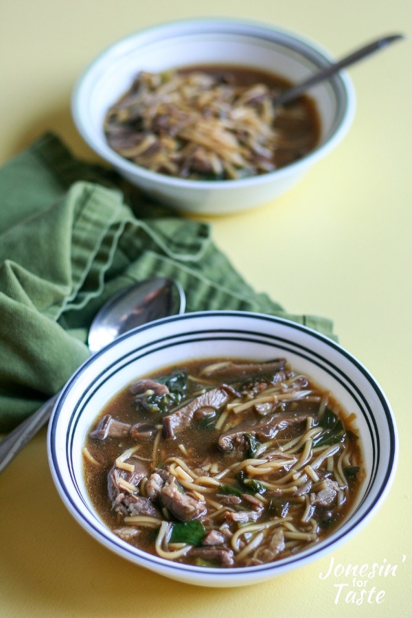 Two bowls of chinese pork shoulder soup on a yellow table