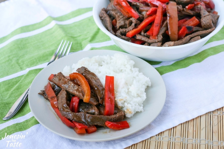A plate of Asian pepper steak next to a fork on a bamboo placemat