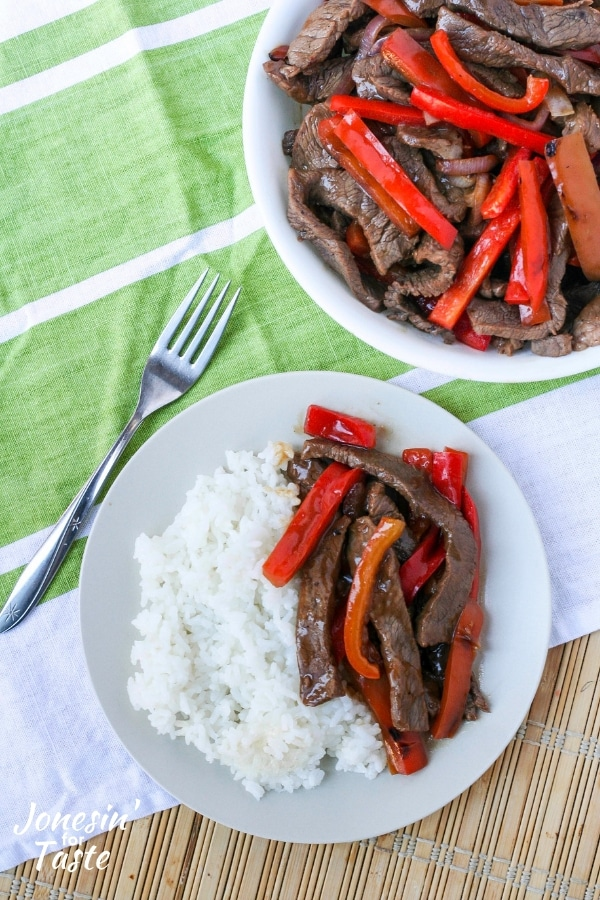 A plate and bowl of Asian pepper steak