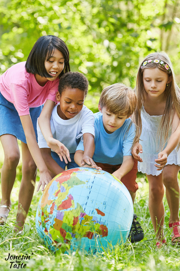 a group of children outside pointing at spots on a globe