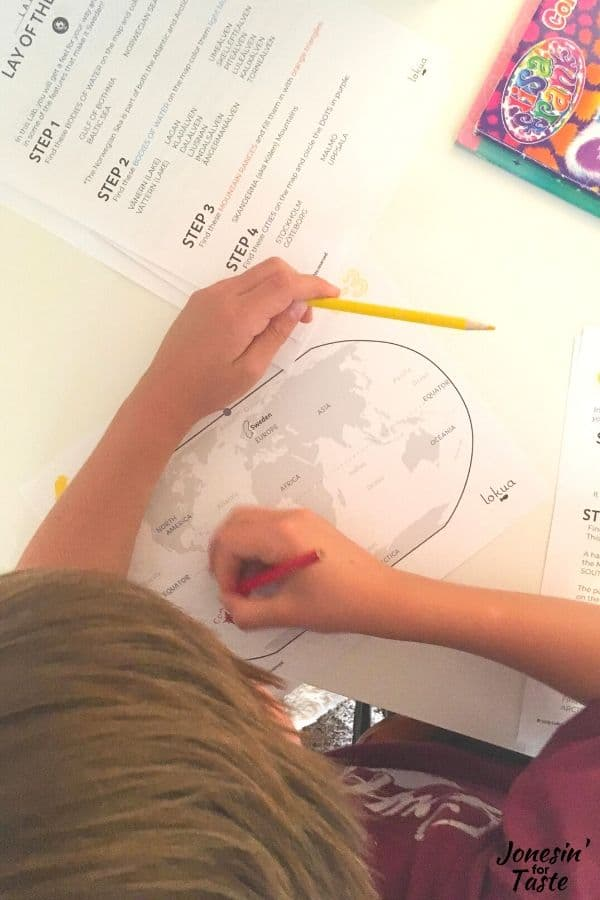 a child doing schoolwork with a world map