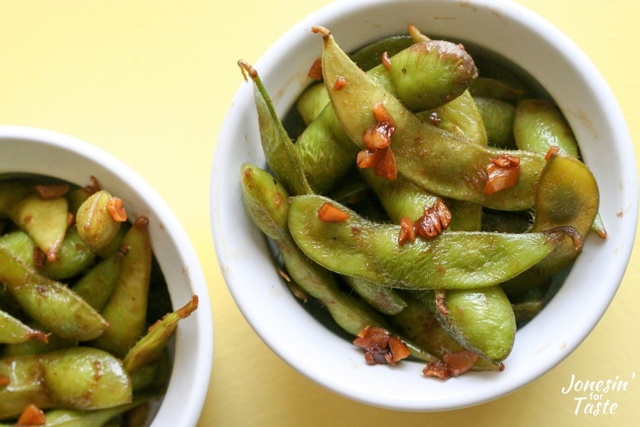 Two white bowls with garlic soy edamame