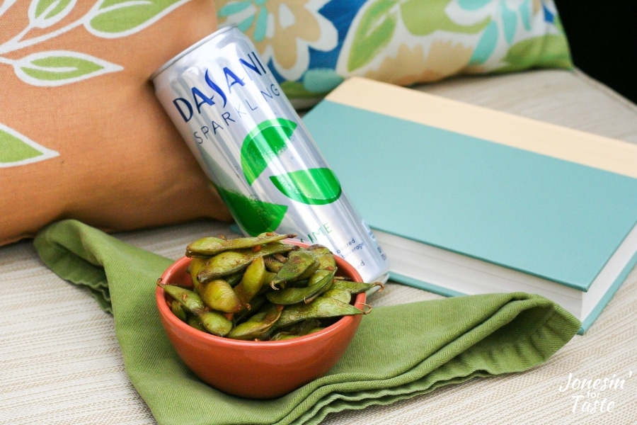 A bowl of garlic soy edamame next to a can of DASANI sparkling next to a book on a chair