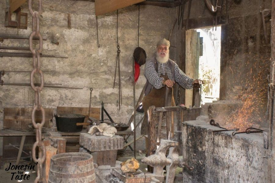 a blacksmith working in his shop at colonial quarters