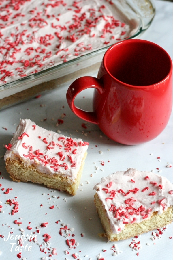 2 iced peppermint cookie bars next to a red mug