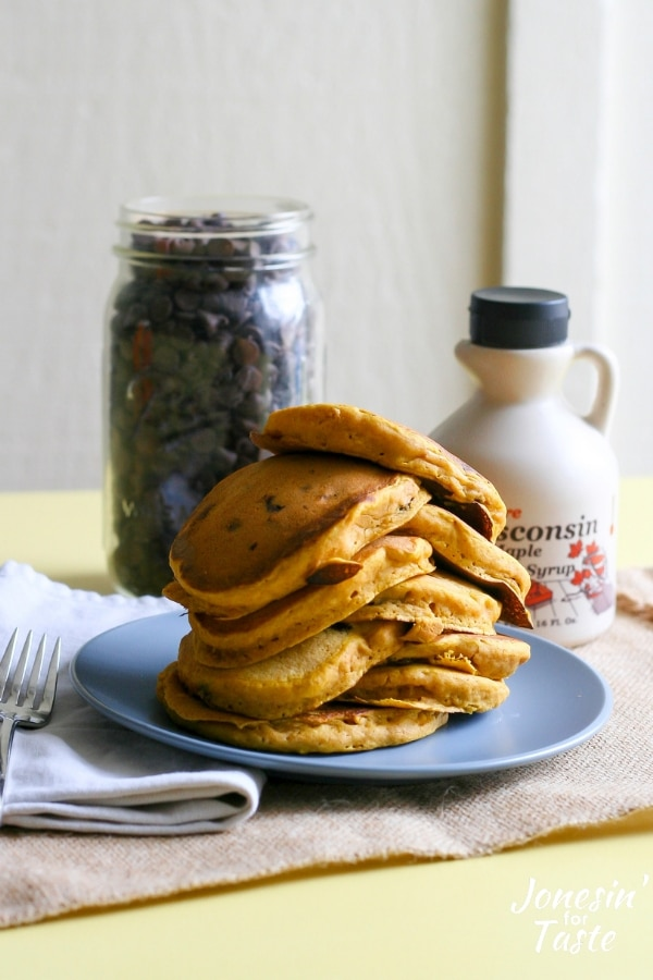 Pumpkin pancakes next to a bottle of maple syrup and a jar of chocolate chips