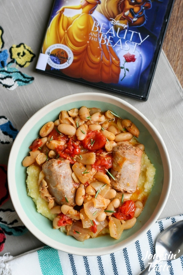 A bowl of polenta, sausage, tomatoes, and beans next to the movie Beauty and the Beast