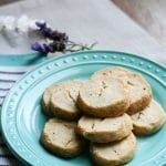 Lavender cookies stacked in layers on a plate.