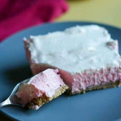 A bite of guava cheesecake on a fork sitting on a blue plate