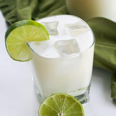 A glass of lemonade with ice and a slice of lime